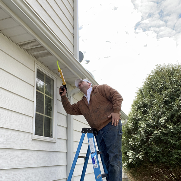 Bat Free technician uses ladder and caulk to seal openings on a home.